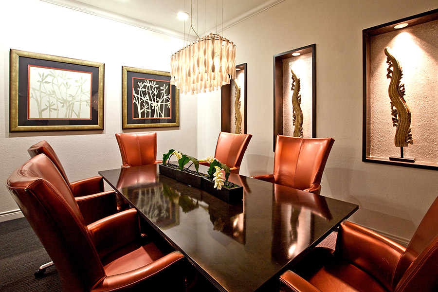 Conference room with large office chairs around smooth table, wall art and decorative chandelier.