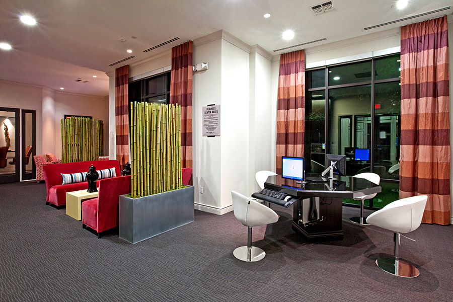 Lobby with carpet, plush couches, bamboo room dividers, and large table with computers.