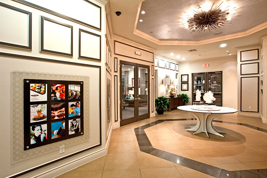 Lobby area with geometric tile floors, modern table, wall art and decorative chandeliers.
