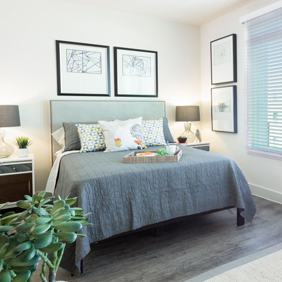 Bedrom with large platform bed with plush bedding and platter with food, wall art, and large window with natural light.