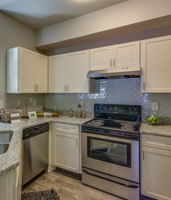 Kitchen with wood floor, white cabinets, gray counters, and stainless steel appliances.