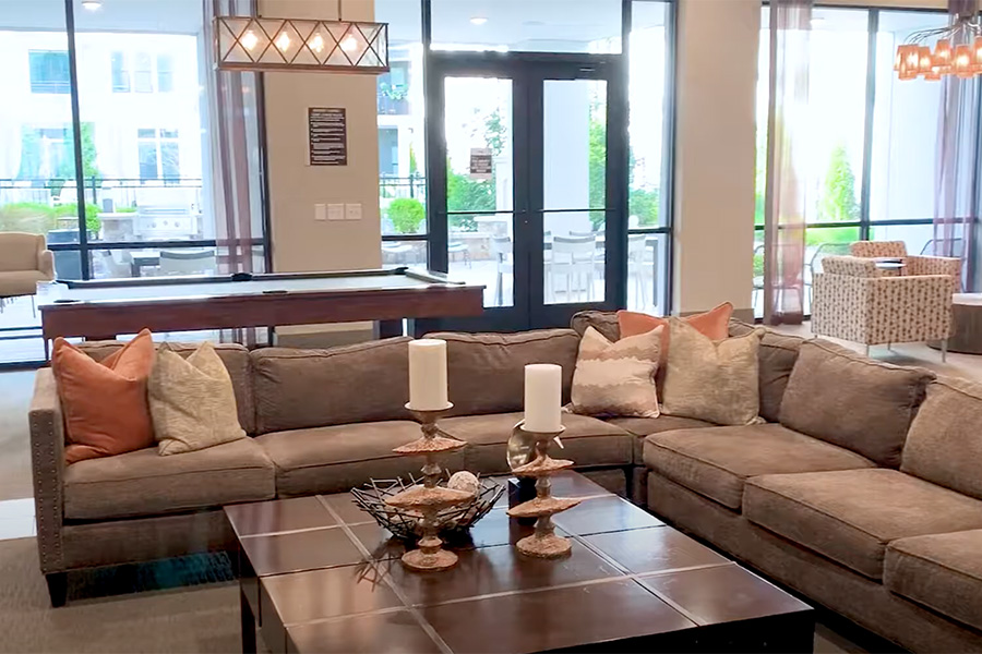 Video tour thumbnail for IMT at the Galleria with lounge area with large sectional couch and coffee table.