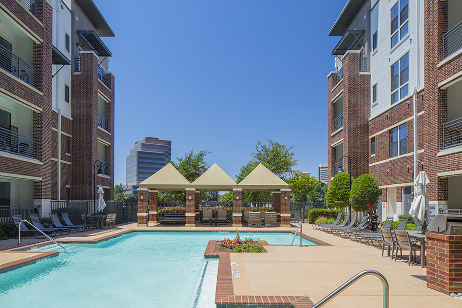 Pool area with paved patio, gazebos, and landscaping overlooked by apartment balconies.
