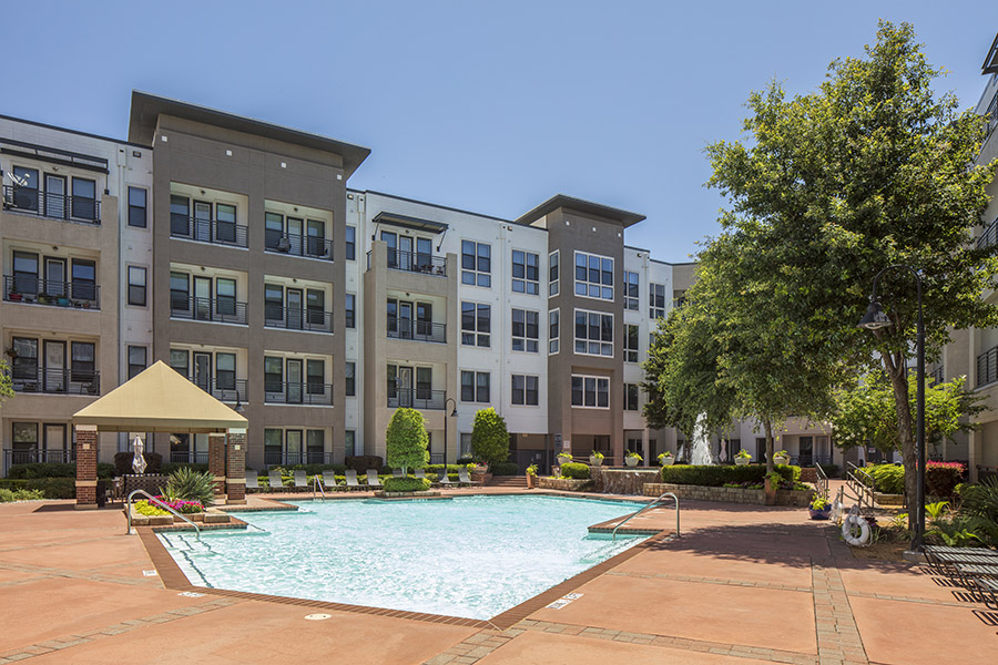 Pool area with paved patio, angular pool, gazebos and tall trees overlooked by apartments.