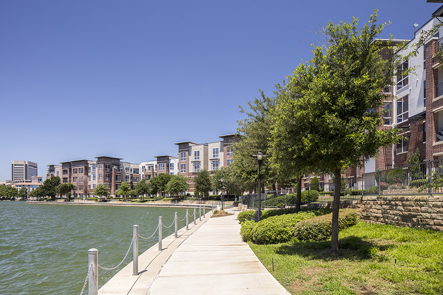Lakeside path with grass and tall trees in front of Lakeshore Lofts apartments.