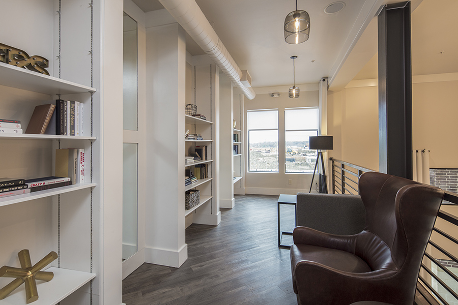 Clubhouse mezzanine with wood floor, comfortable chairs, built in bookshelves, and large windows.