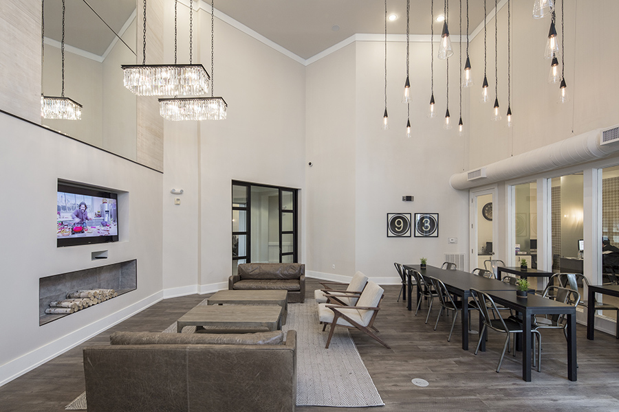 Lounge with wood floor, leather couch with tables, fireplace, TV, and decorative pendant lights.