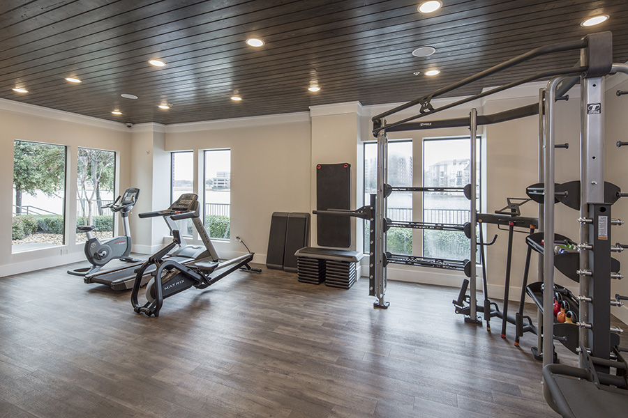 Fitness center with wood floor, weight and cardio equipment, and large windows.