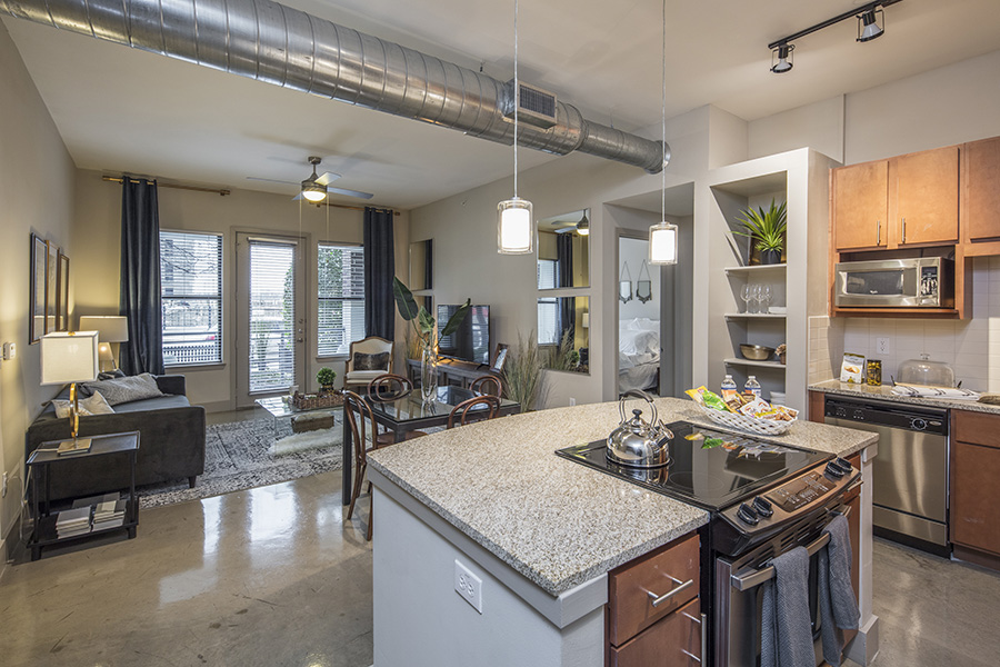 Kitchen and living area with polished concrete floor, kitchen island, and large windows and door to balcony.