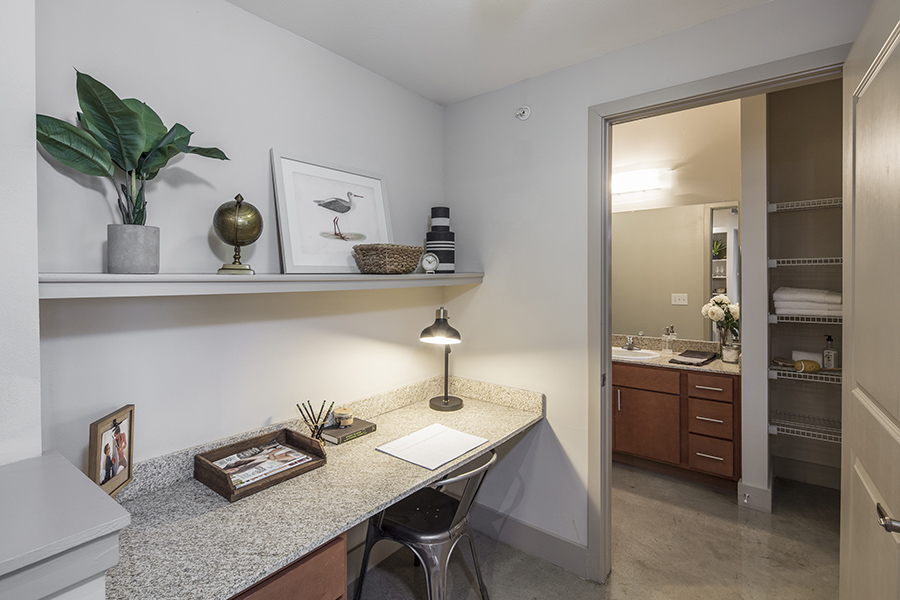 Apartment workspace with built in desk and shelf with decor, metal chair, and doorway to bathroom.