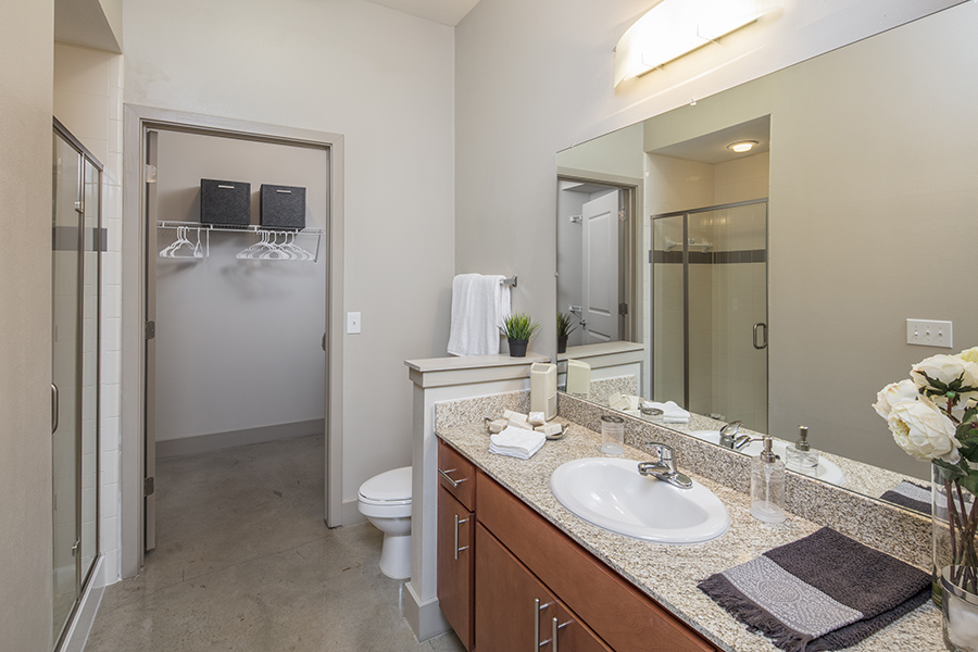 Bathroom with polished concrete floor, wood cabinets, light counter, large mirror, and closet door.