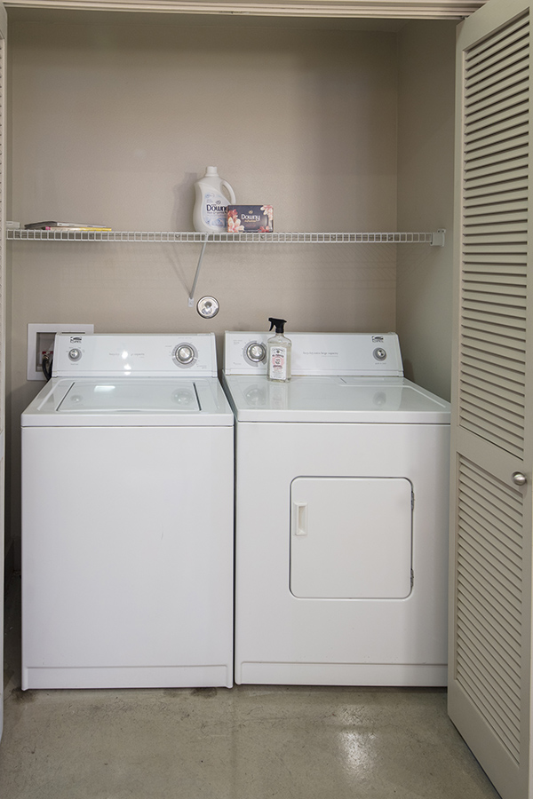 Laundry closet with washer and dryer machines and shelf.