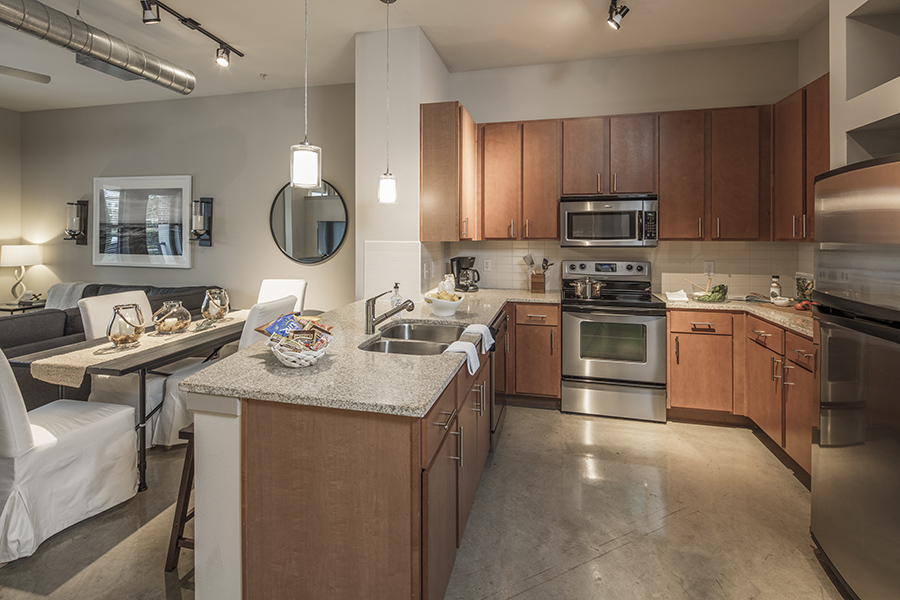 Kitchen with polished concrete floor, wood cabinets, light counters, and stainless steel appliances.