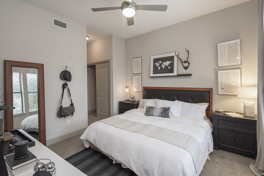 Bedroom with carpet, large bed with plush bedding, ceiling fan, and wall art.