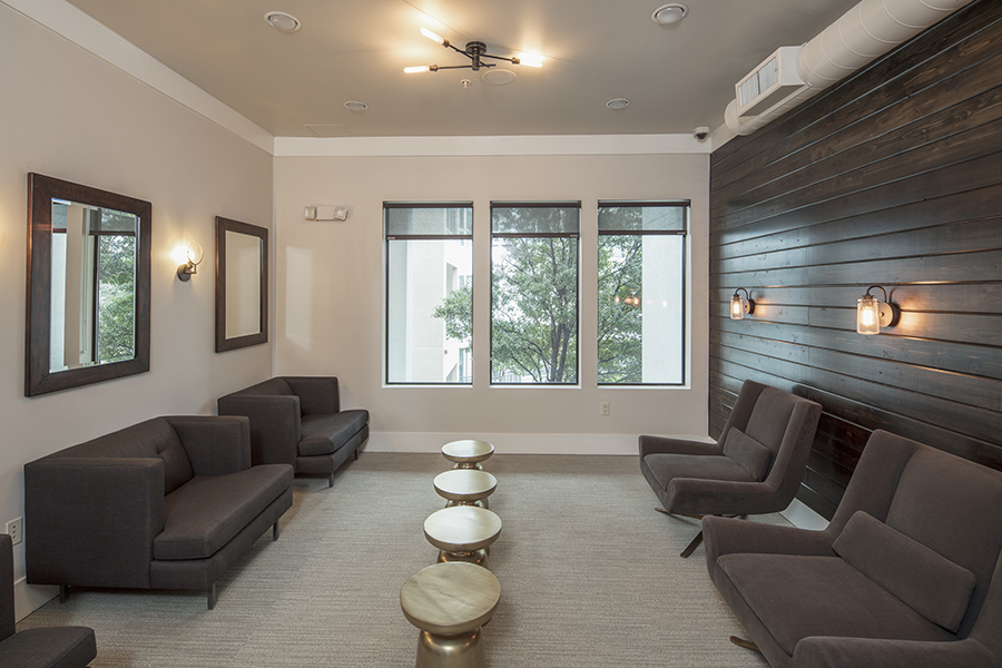 Lounge with comfortable plush seats, metal coffee tables, dark accent wall, and large windows.