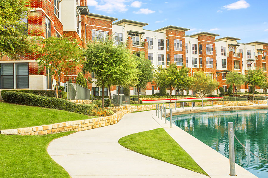Lakeshore Lofts apartments with lakeside walkways and tall trees.