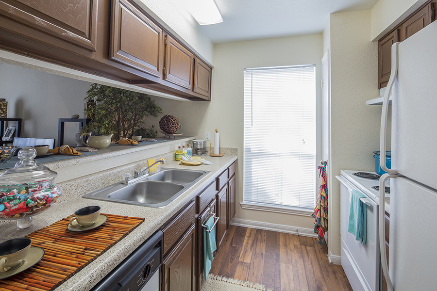 kitchen with peeking dining view area, hardwood floors leading to a long ceiling to floor window, updated white appliances and stainless steel sink with dark brown cabinets
