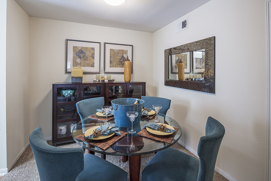 dining room area decorate with glass circular table four set place matts and real velvet blue chairs surrounding table