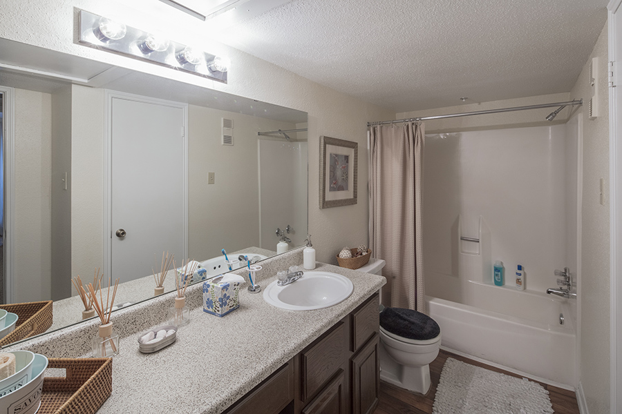 apartment bathroom showing granite countertops with dark wood cabinets and matching floors, full length mirrors, and tiled tub and shower combination
