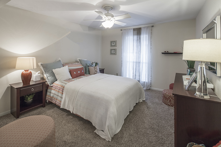 Apartment bedroom with plush carpet floors decorated bed with striped and white duvet, matching rich wood bedside table and matching dresser with comfortable fabric sitting stool