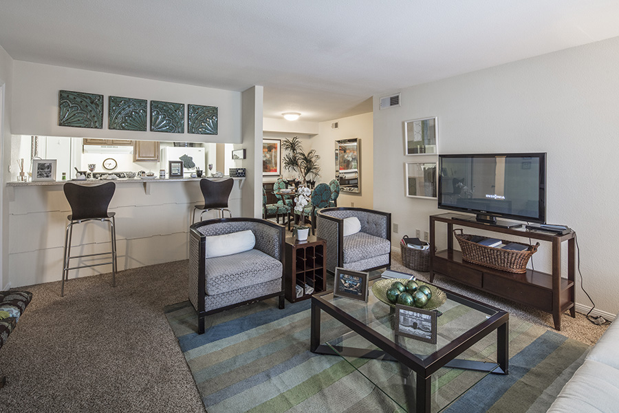apartment living area with plush carpeted floors leading to dining area and kitchen bar area with two barstools, two luxury chairs face a wood and glass coffee table in living space