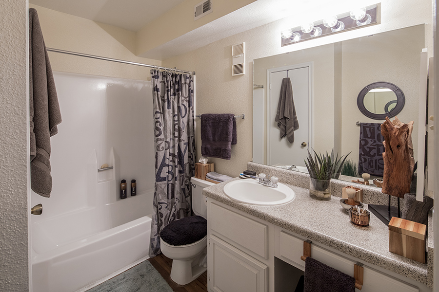bathroom with hardwood floors leading to tiled shower and tub combination, toilet, ceramic white sink on vinyl countertops and white wood cabinets