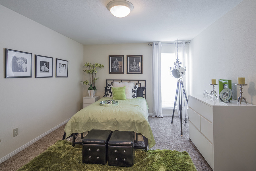 natural light bedroom with plush carpet floors eggshell walls with white trim, room decorated with twin bed, green duvet and white dresser