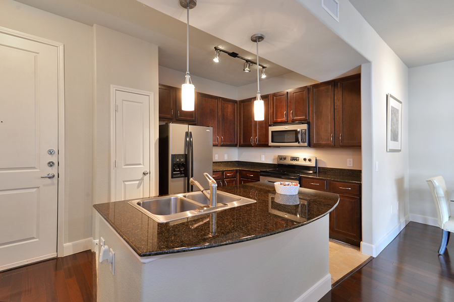 Kitchen with wood floor, wood cabinets, dark counter, and stainless steel appliances.