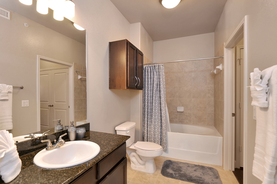 Bathroom with wood cabinets, dark counter, large mirror, and shower tub with curtain.