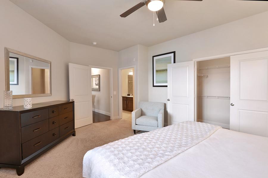Bedroom with carpet, plush bedding, large wood dresser, mirror, and door to walk in closet.