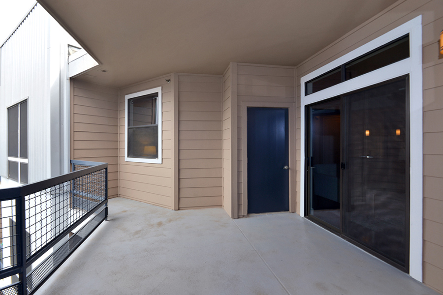 Large balcony with metal railing and sliding door to apartment.
