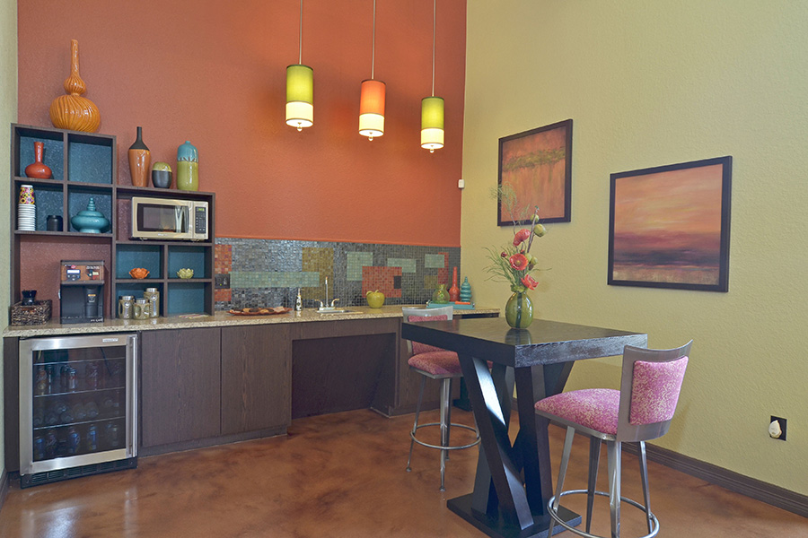community kitchen and cafe decorate with mini fridge a microwave and coffee maker with wood cabinets on marble floors and wood standing table nearby