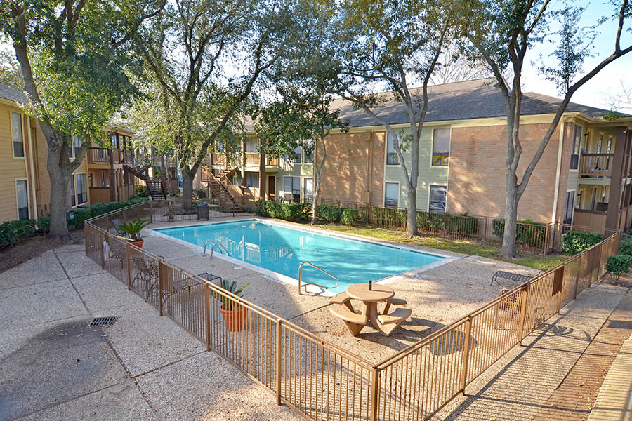 community gated pool area surrounded by planters stone picnic tables and shaded by four large trees taller tan apartment building