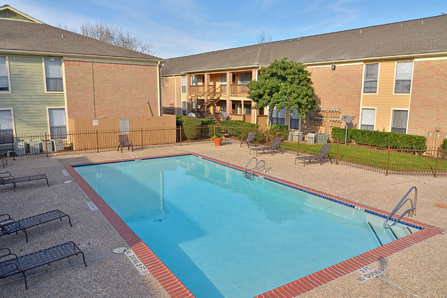 outdoor gated pool a walk away from apartment units surrounded by luxury loungers and trees
