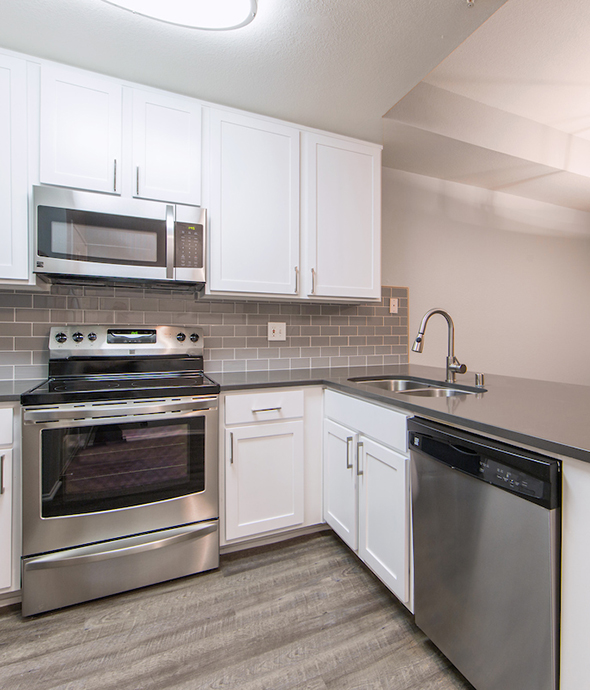 Kitchen with wood floors, white cabinets, dark counters and stainless steel appliances.