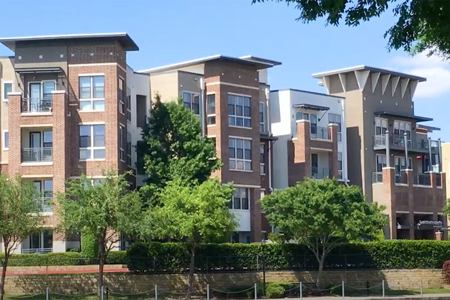 Video tour thumbnail for Lakeshore Lofts with 4 story apartments, tall trees and lush landscaping.