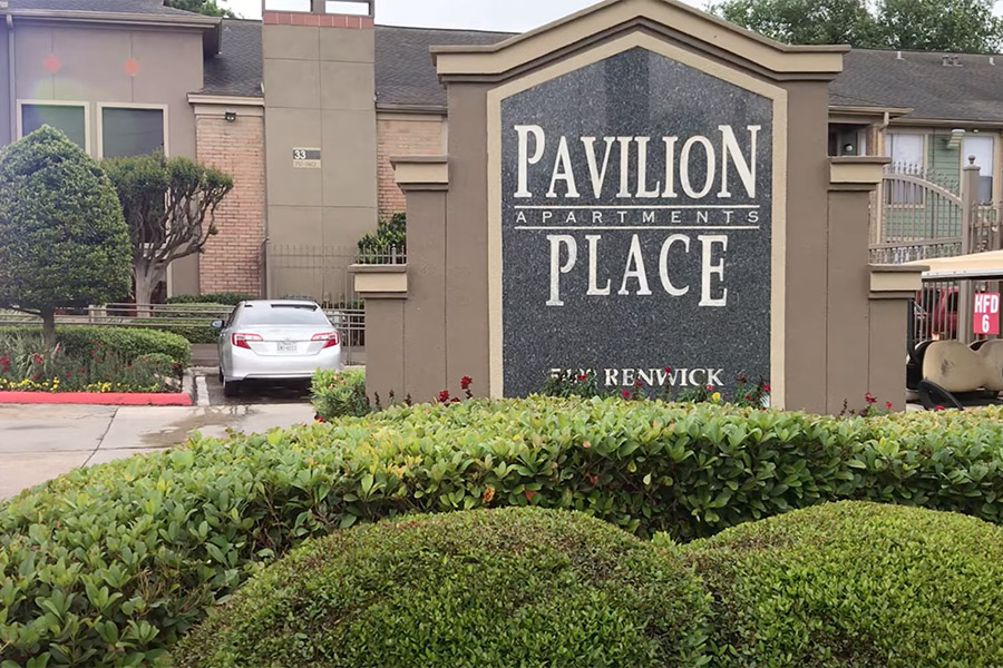 Video tour thumbnail for Pavilion Place with large monument sign, lush green bushes and apartments behind.