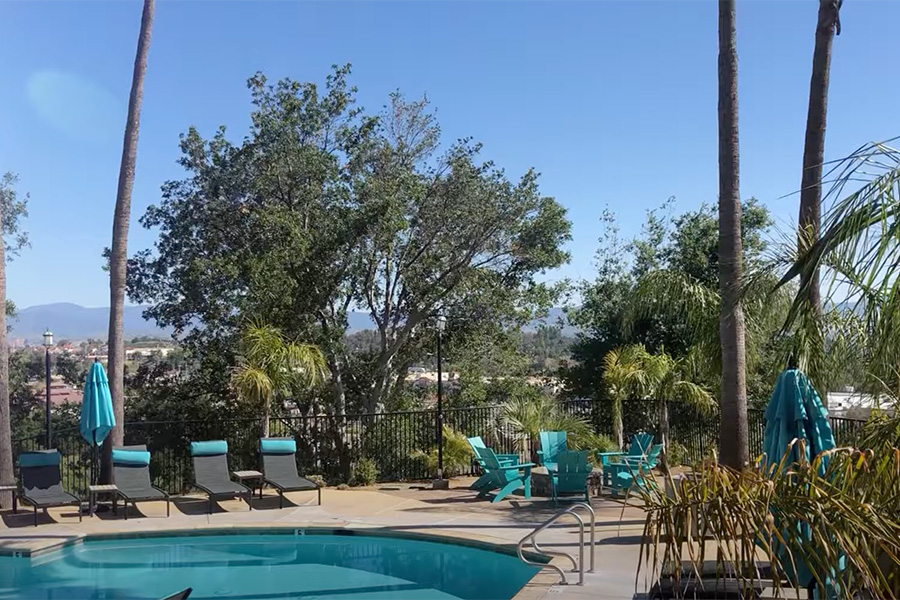 Video tour thumbnail for Stevenson Ranch with pool area, lounge chairs, and tall trees.