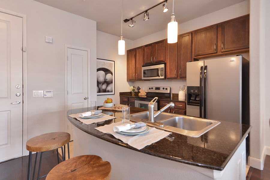 Kitchen with wood cabinets, dark counter, stainless steel apartments, and pendant lights above breakfast bar.