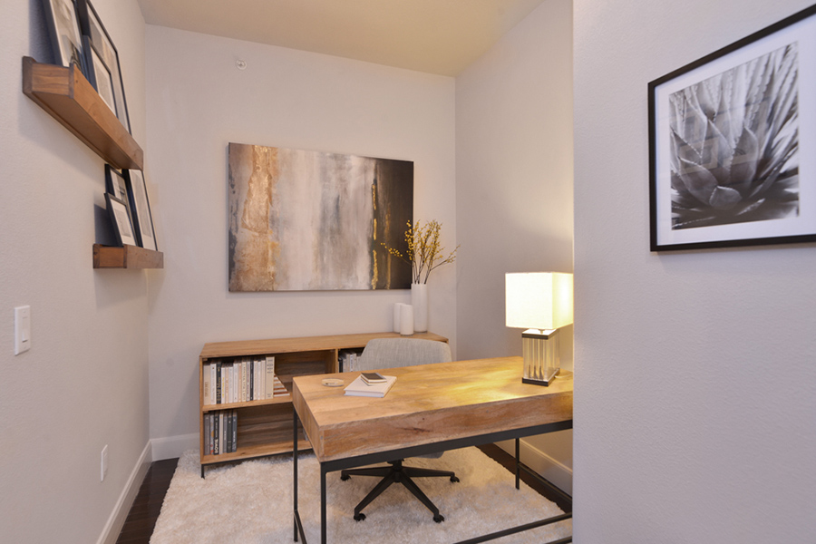 Office space with desk, lamp, low bookshelf, and wall art decor.