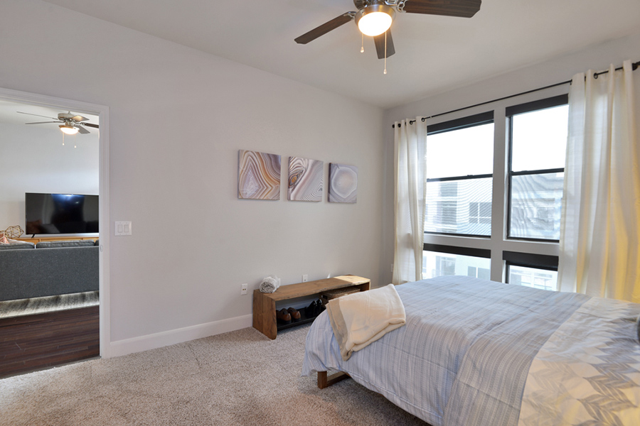 Bedroom with carpet, low bed with plush bedding, ceiling fan, and large windows.