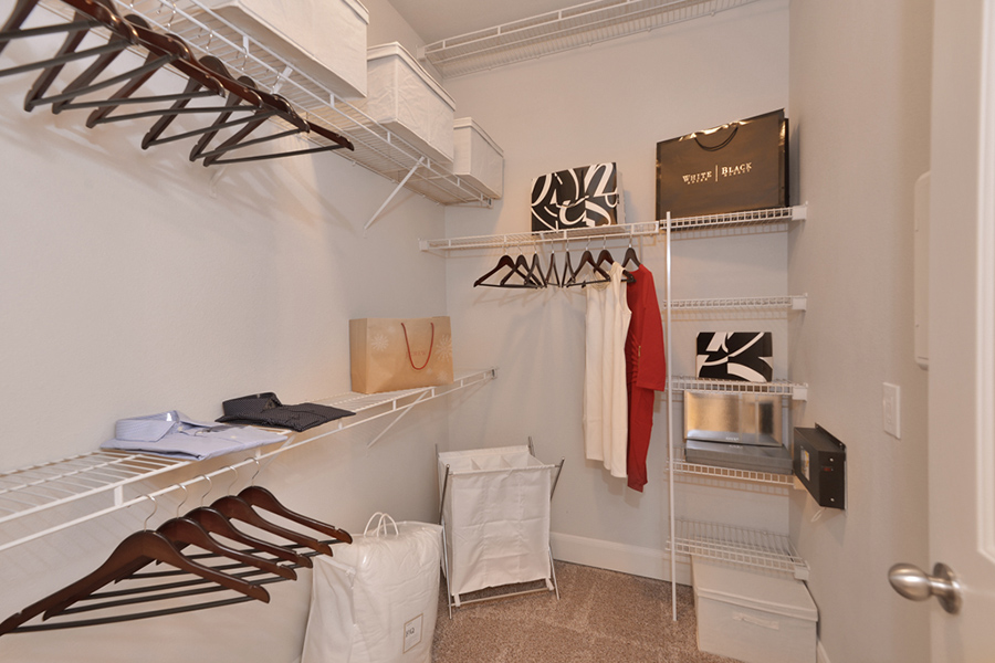 Walk in closet with carpet, built in wire shelving, and clothes on hangers.