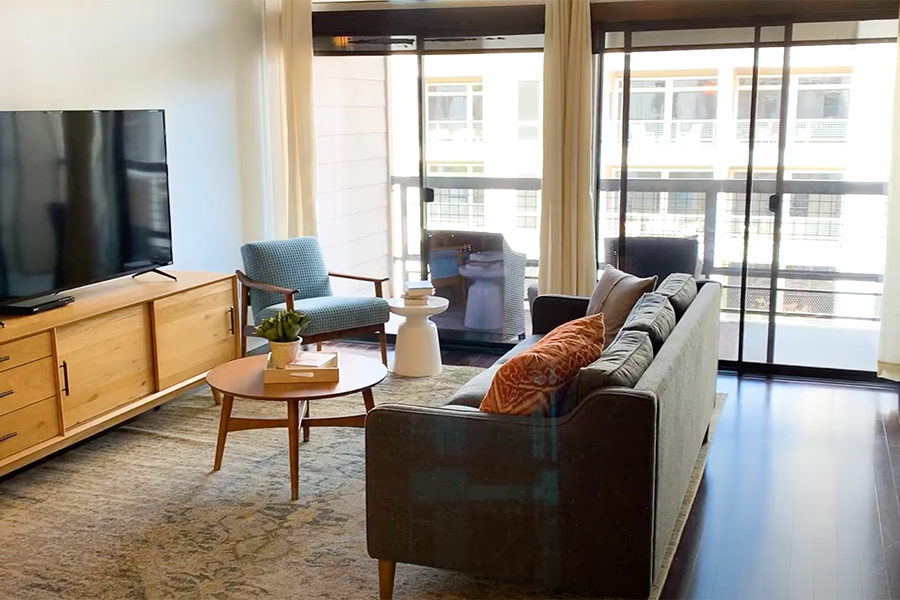 Video tour thumbnail for Uptown Post Oak with apartment living room, large windows, couch and TV.