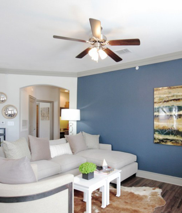 Living room with wood floor and rug, plush sectional couch and chairs, ceiling fan, and large wall art.