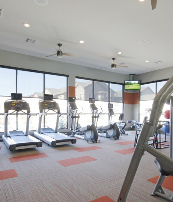 Fitness center with carpet floor, high ceilings with fans, wall mounted TVs, and rows of cardio equipment in front of large windows.