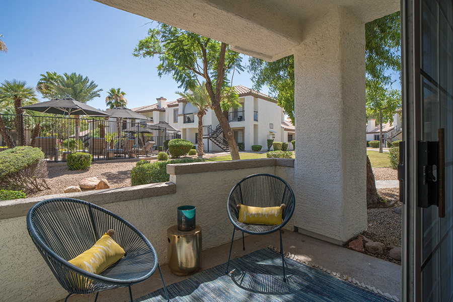 Patio overlooking pool area with outdoor chairs and pillows.