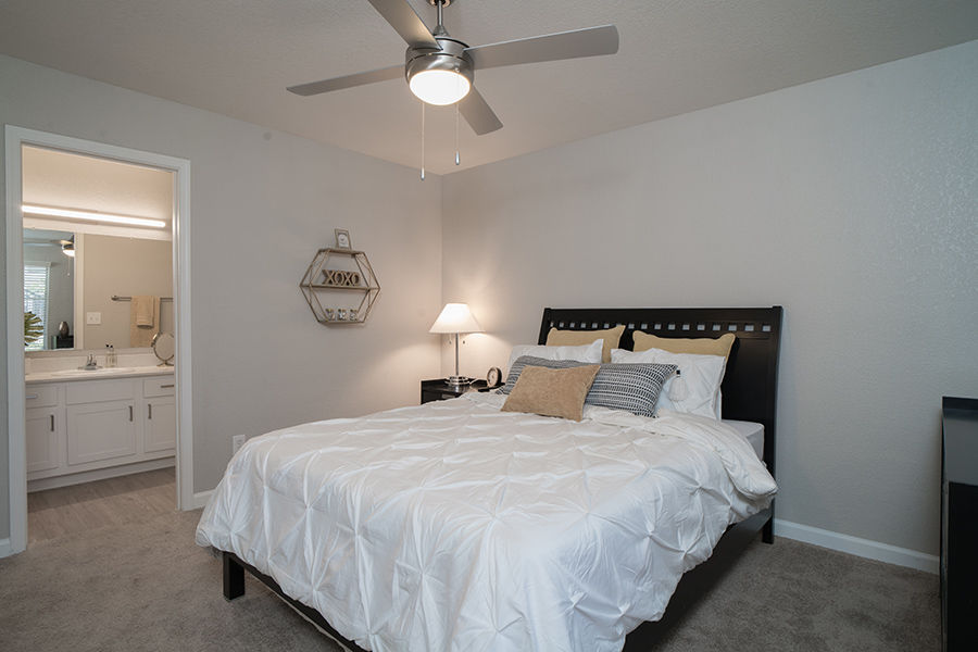 Bedroom with large platform bed, ceiling fan, decorative wall art, and door to bathroom.