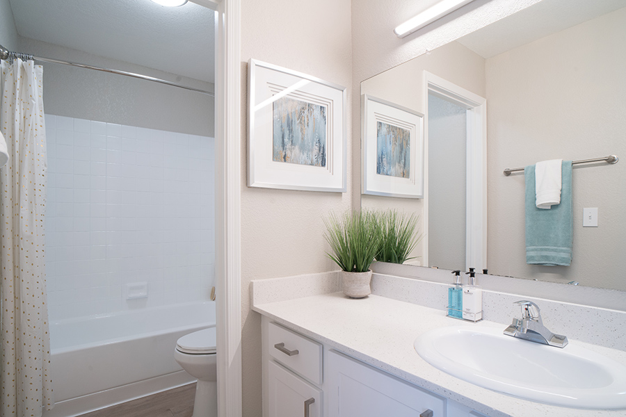 Bathroom with white cabinets and counter, large lighted mirror, and tiled shower tub with curtain.