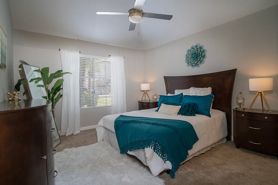 Bedroom with carpet floor, large plush bed with wood headboard, rich wood furniture, and large window.