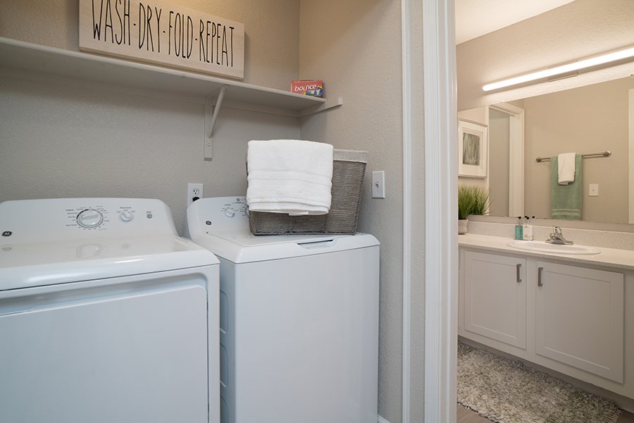 Laundry room with washer and dryer, basket with towels, shelf, and door to bathroom.